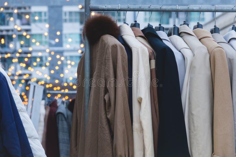 Abrigos de invierno colgados en un estante de la ropa foto de archivo libre de regalías