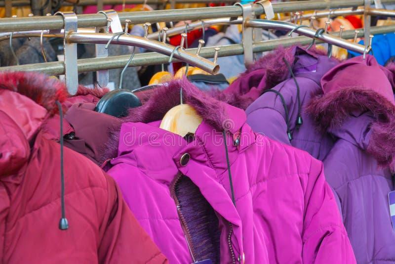 Abrigos de invierno de la moda colgados en un estante de la ropa imagen de archivo