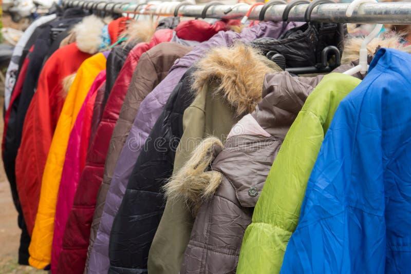 Abrigos de invierno de la moda colgados en un estante de la ropa imágenes de archivo libres de regalías