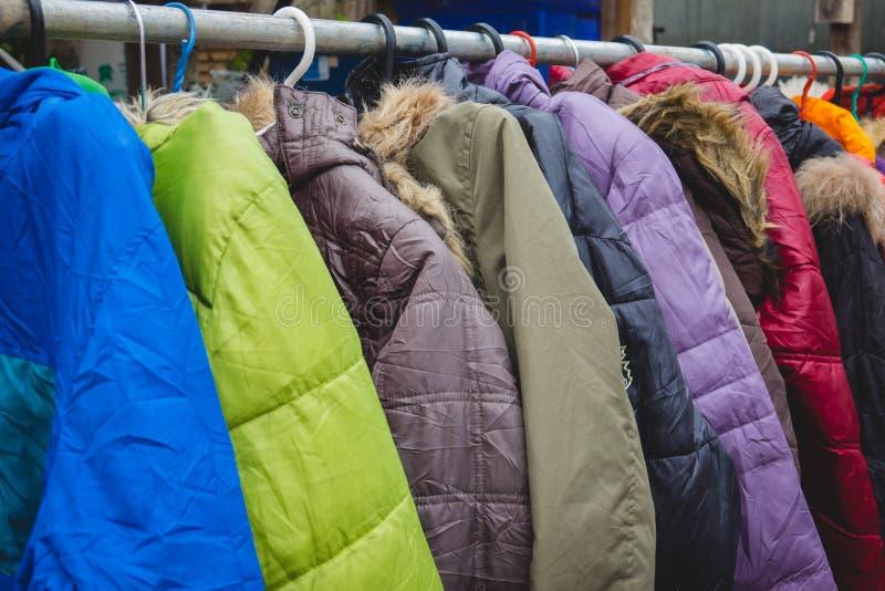 Abrigos de invierno de la moda colgados en un estante de la ropa imagenes de archivo