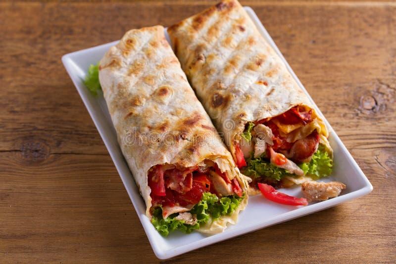 Abrigos de la ensalada César del pollo con tocino, los tomates, la lechuga y el queso La tortilla, burritos, bocadillos torció lo fotografía de archivo libre de regalías