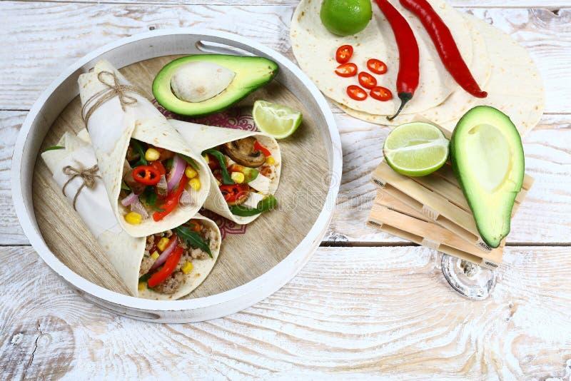 Abrigos de los Burritos con el pollo y las verduras en fondo ligero E imágenes de archivo libres de regalías