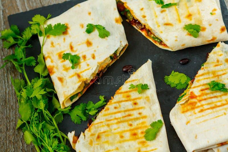 Abrigos vegetarianos de los burritos con las habas, el aguacate y el queso en una pizarra imagen de archivo