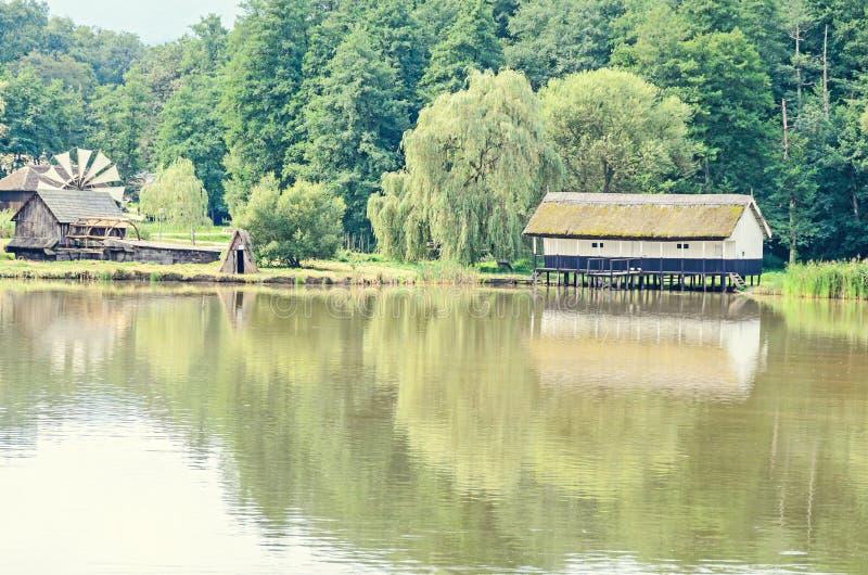 Abrigue a construção na água, telhado da palha, perto do lago do watermill e do verde imagens de stock royalty free