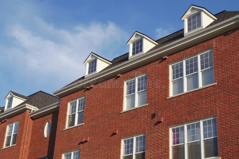 Abrigue a fachada residencial da parede de tijolo vermelho do trapeira da claraboia do telhado fotos de stock royalty free