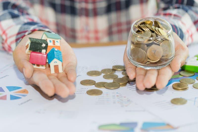 Abrigue modelos e invente-os nas mãos humanas, conceito da hipoteca pela casa do dinheiro das moedas fotografia de stock royalty free