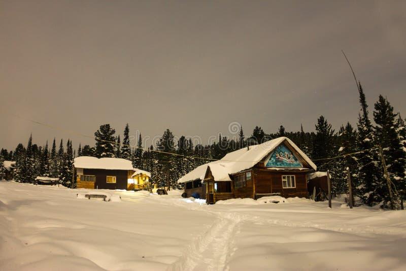 Abrigue o chalé durante uma queda de neve na floresta do inverno das árvores no nig fotos de stock royalty free