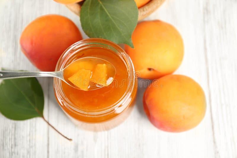 Abrikozen eigengemaakte jam in kruik met lepel en rijp sappig fruit stock afbeelding