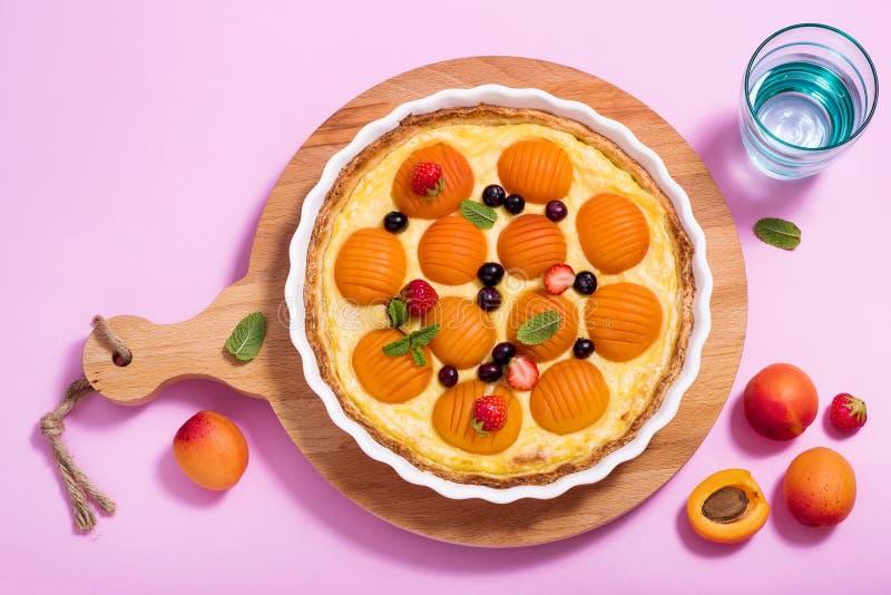 Abrikozenpastei of scherpe die vers in ronde vorm op roze achtergrond, fruitcake, de zomerdessert wordt gebakken royalty-vrije stock foto