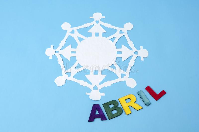 Abril gjorde från färgrika träbokstäver och pappers- dockakedja arkivfoto