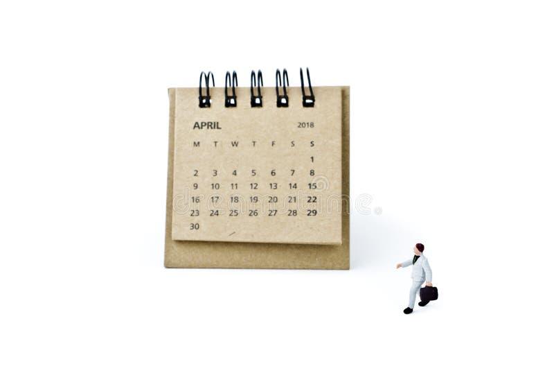 abril Haga calendarios la hoja y al hombre de negocios plástico miniatura en blanco foto de archivo libre de regalías