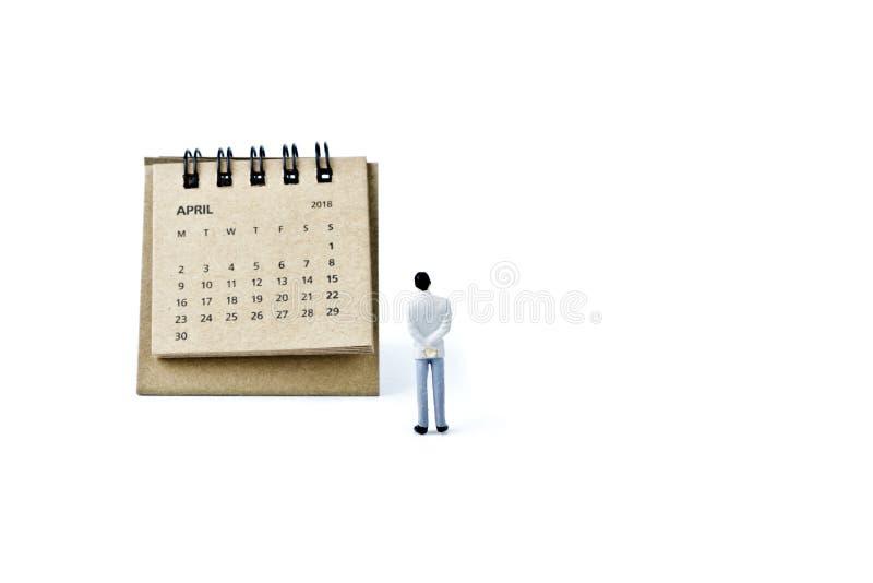 abril Haga calendarios la hoja y al hombre plástico miniatura en el backgro blanco imagenes de archivo