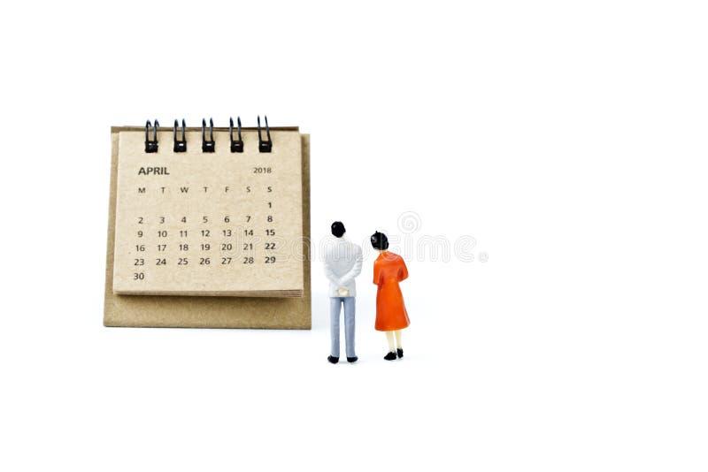 abril Haga calendarios la hoja y hombre y mujer plásticos miniatura en whi fotografía de archivo