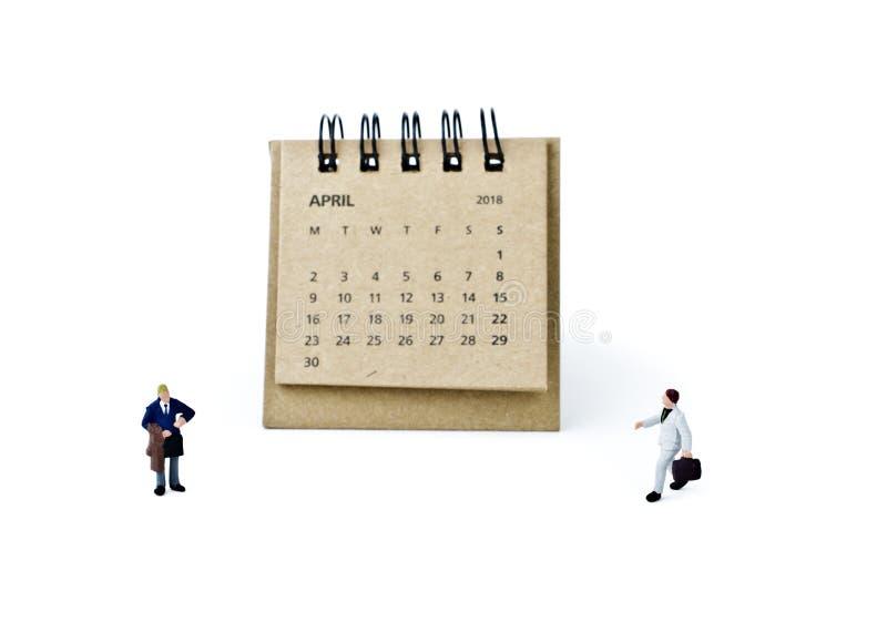 abril Haga calendarios la hoja y a los hombres de negocios plásticos miniatura en blanco foto de archivo