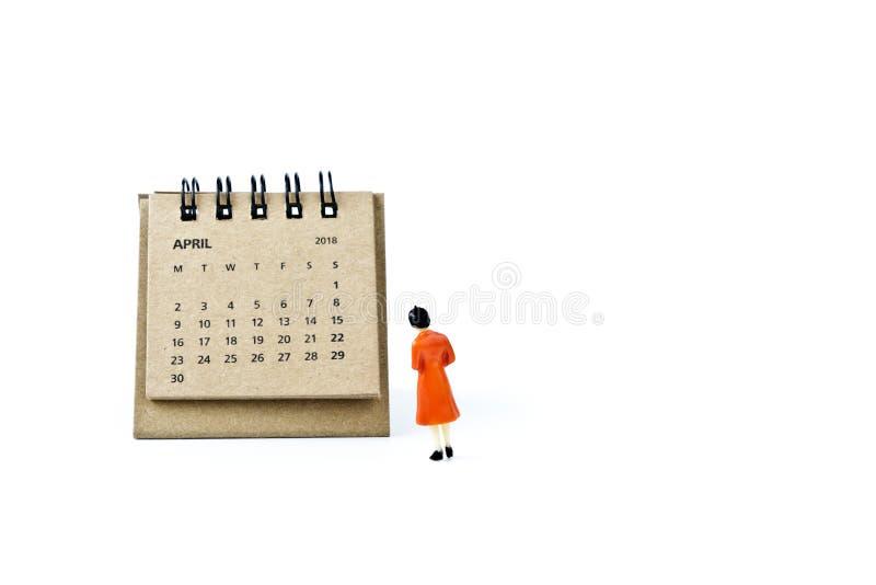 abril Haga calendarios la hoja y a la mujer plástica miniatura en el backg blanco imagen de archivo