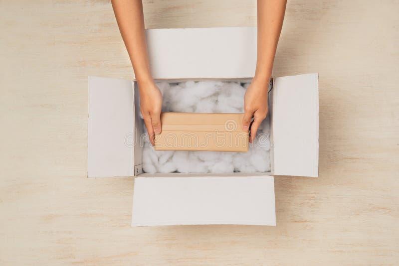 Abrindo uma caixa da caixa Mãos que guardam a caixa de presente na caixa de cartão fotografia de stock