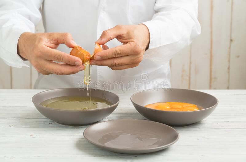 Abrir um ovo orgânico nas mãos do cozinheiro para separar a gema de ovo foto de stock