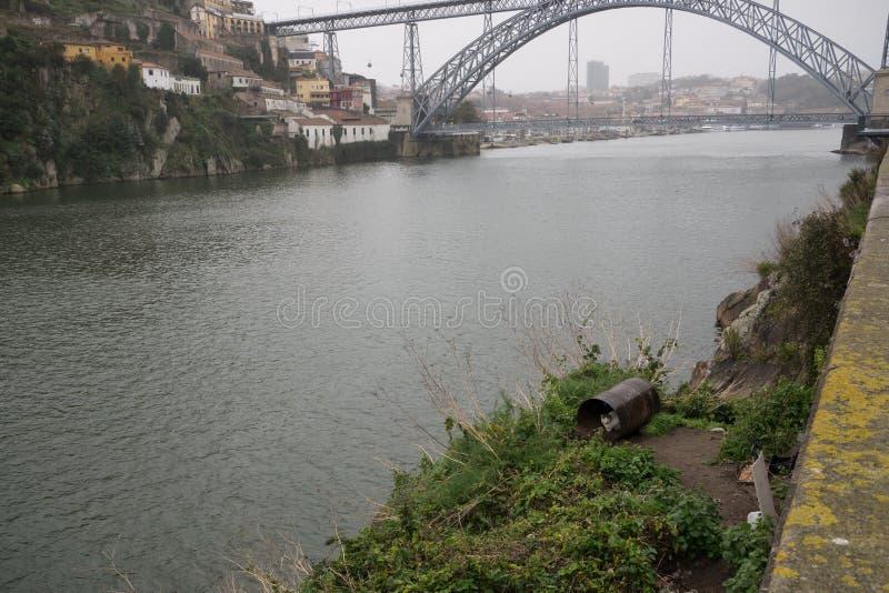 Abris de chat de pluie dans le vieux baril en métal sur des banques de rivière Douro à Porto, Portugal avec le pont à l'arrière-p images stock