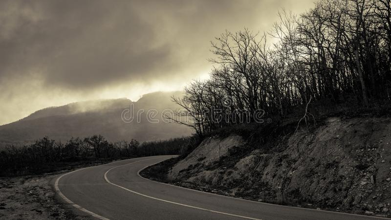 Abrupt turn of mountain road among the bare autumn wood stock images