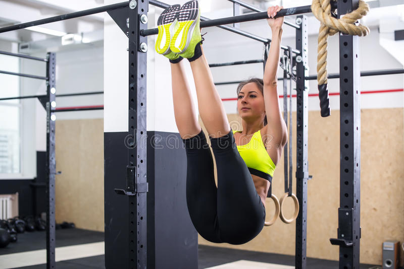 Abs apto do treinamento da menina levantando os pés em uma barra horisontal Exercício da mulher da aptidão que faz exercícios no  imagem de stock