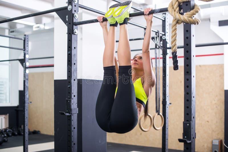 ABS convenable de formation de fille en soulevant des jambes sur une barre horisontal Séance d'entraînement de femme de forme phy photographie stock libre de droits