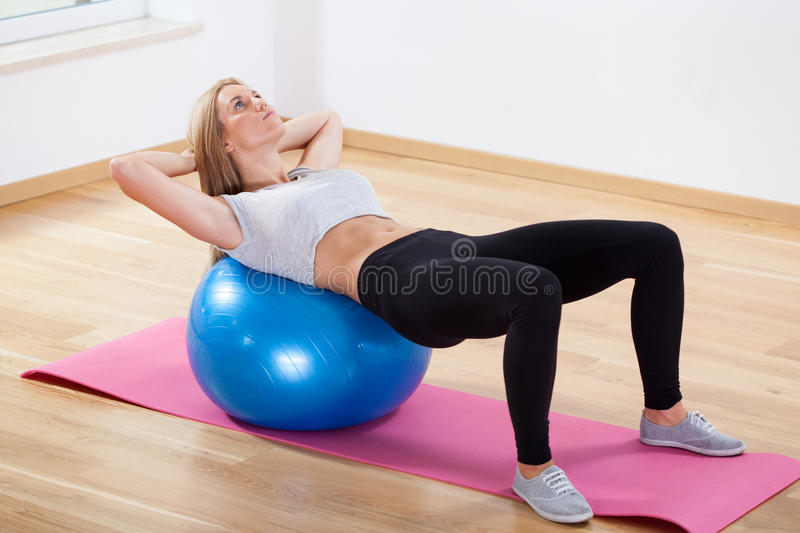 Abs training on fitness ball. Woman doing abs training on fitness ball stock photo