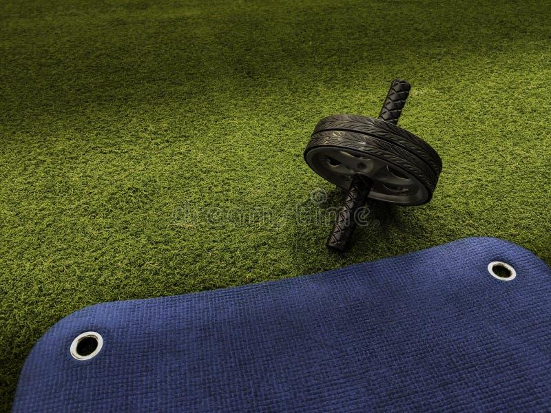 Abs wiel op groen kunstmatig gras en blauwe opleidingsmat stock foto