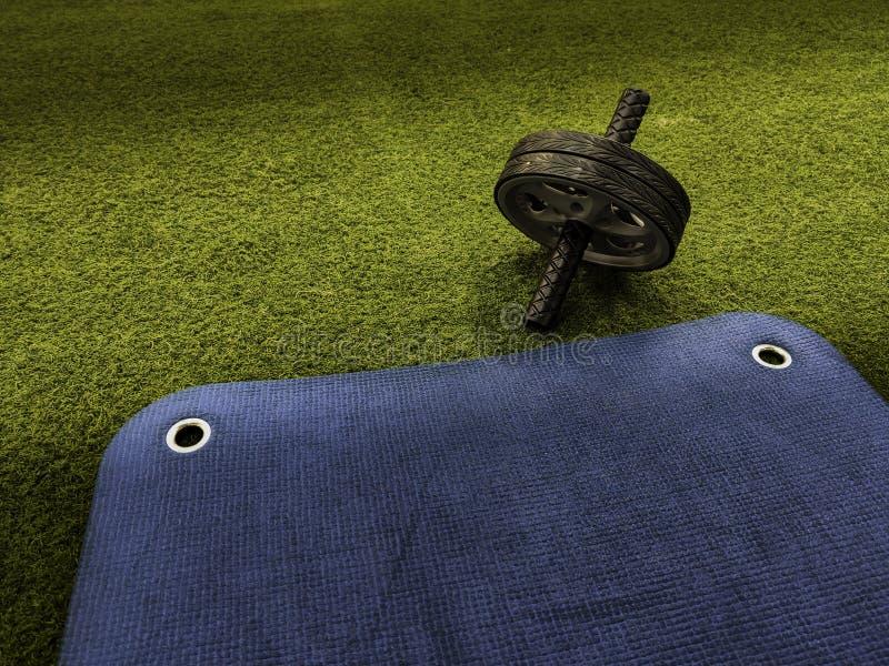 Abs wiel op groen kunstmatig gras en blauwe opleidingsmat royalty-vrije stock foto's