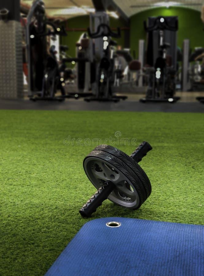 Abs wiel op groen kunstmatig gras en blauwe opleidingsmat stock afbeelding