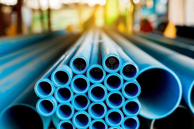 Abschluss bis zum blauen Kunststoffrohrhintergrund, PVC-Rohre gestapelt im Lager stockbilder