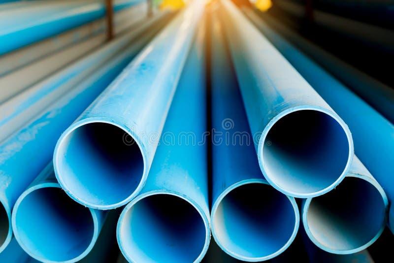 Abschluss bis zum blauen Kunststoffrohrhintergrund, PVC-Rohre gestapelt im Lager stockfotos
