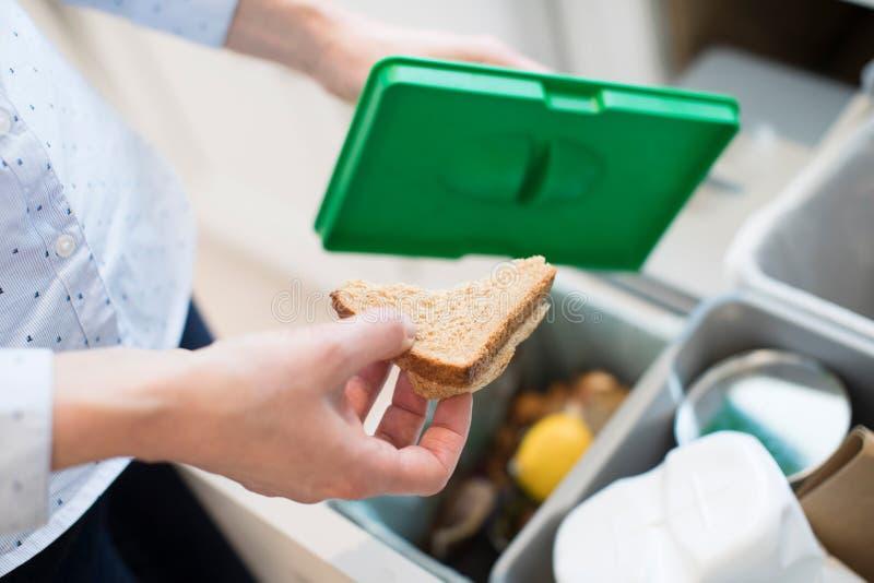 Abschluss der Frau Lebensmittelabfälle in Wiederverwertungs-Behälter in der Küche setzend lizenzfreies stockbild