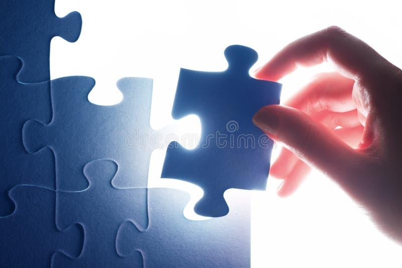 Abschluss des letzten Stückes des Puzzlen lösung stockbilder