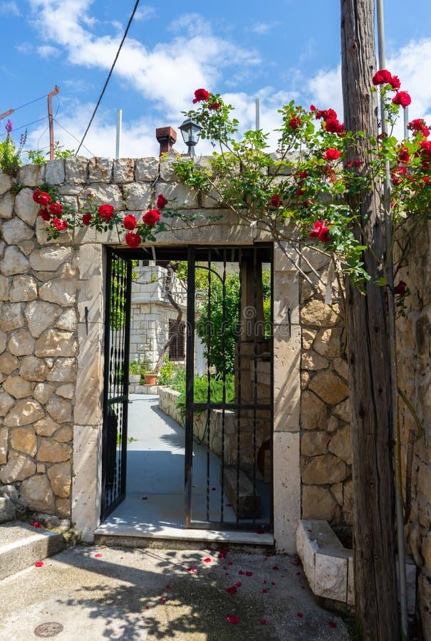 Abschluss herauf alte Haustür des Retrostils der Mittelmeerarchitekturkultur Metallzaun-Eingangsfassade mit Steinwand und Rosen lizenzfreies stockfoto