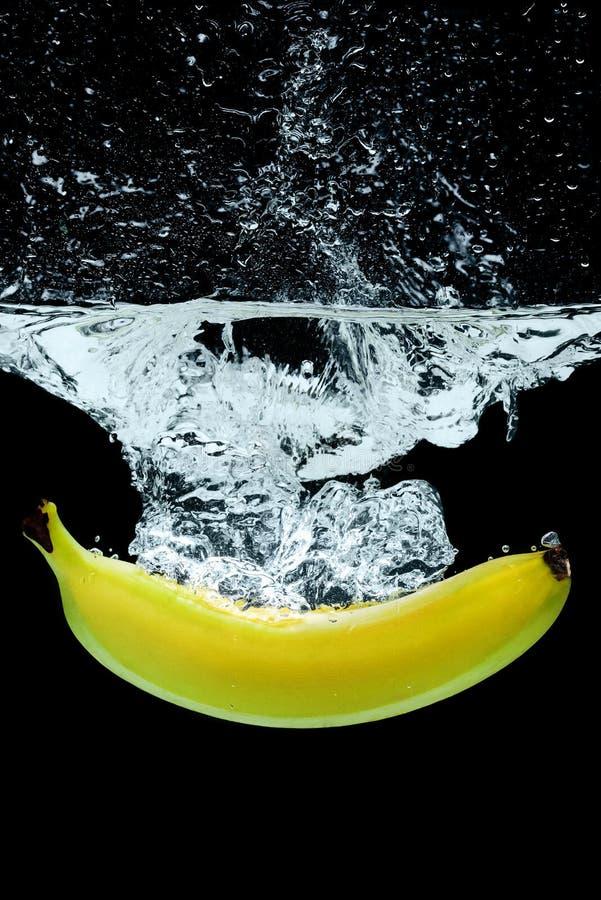 Abschluss herauf Ansicht der Banane im Wasser mit spritzt lizenzfreie stockfotos