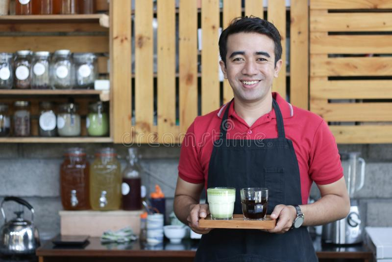 Abschluss herauf asiatisches Mann barista, das den Laptop halten überprüft Aufträge und Vorrat hinter dem Zähler lächelt Caféinha stockfotos