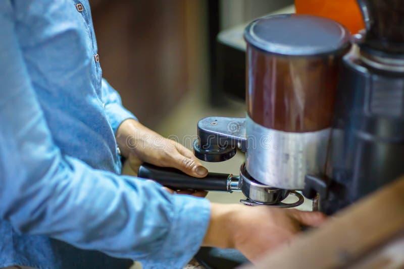 Abschluss herauf Barista reibt frisch briet durch Kaffeemühle machen Bohnen in ein Pulver stockbild