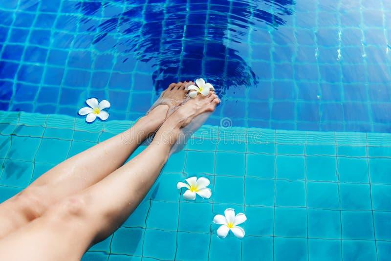 Abschluss herauf Beinlebensstilfrau, bei der Badeanzugentspannung und den Badekurort so glücklich mit Cocktail auf Liege nahe Swi lizenzfreie stockfotografie