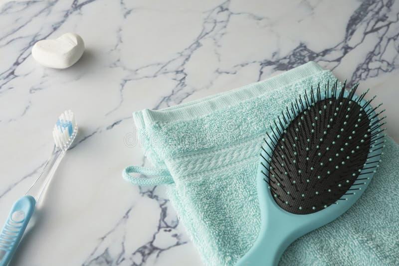Abschluss herauf blauen Waschlappen, Bürstenseife und Zahnbürste auf Marmorplatte lizenzfreies stockfoto