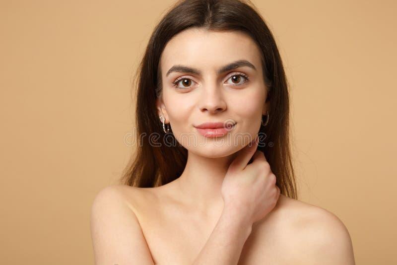 Abschluss herauf brunette halb nackte Frau 20s mit perfekter Haut, Hand auf dem Hals lokalisiert auf beige Pastellwandhintergrund lizenzfreies stockfoto