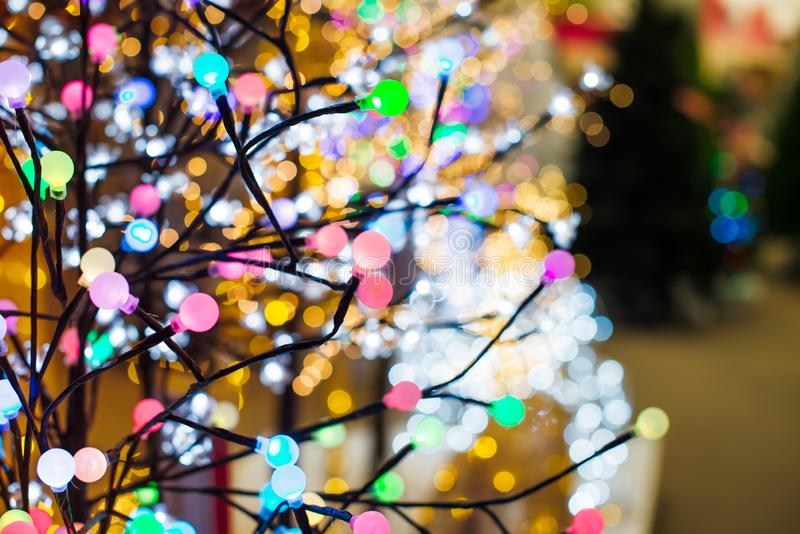Abschluss herauf bunte Birnenlichter auf Baumformgirlande auf dem Hintergrund von verschiedenen glühenden Weihnachtslichtern im G stockfotografie