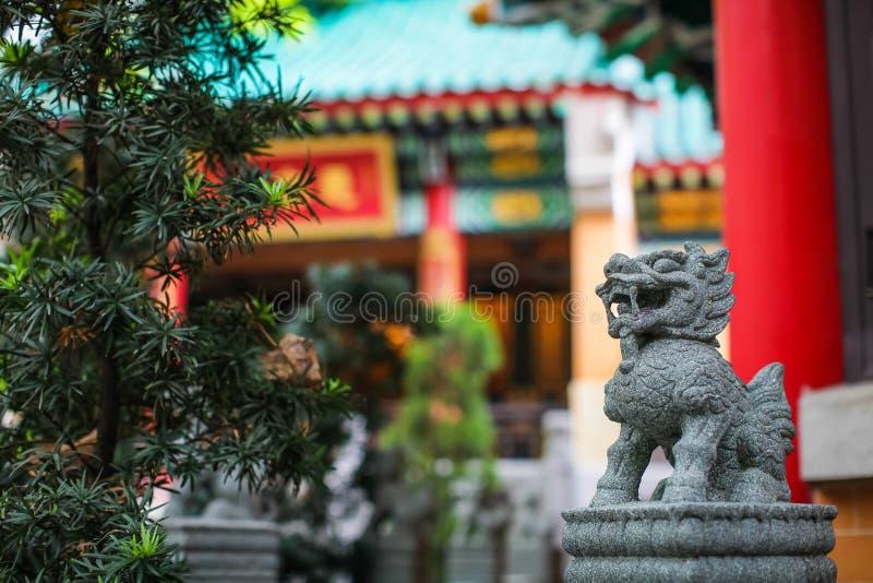 Abschluss herauf chinesischen Löwe oder Drachesteinfigürchen auf unscharfem Tempelhintergrund lizenzfreie stockbilder