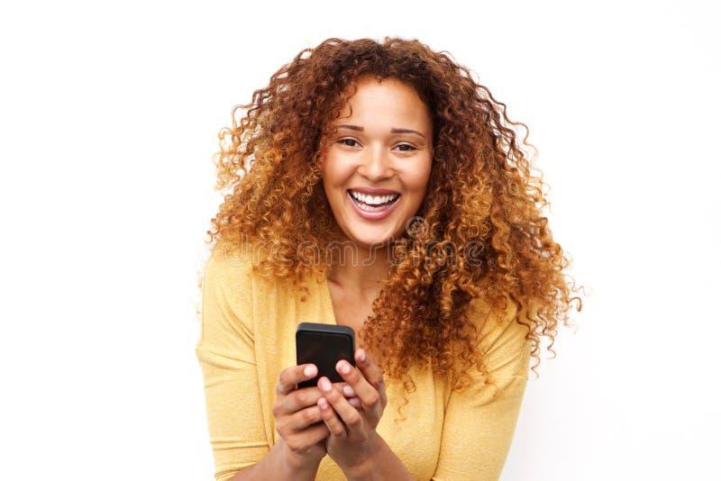 Abschluss herauf das Lachen der jungen Frau mit Handy gegen weißen Hintergrund lizenzfreies stockfoto