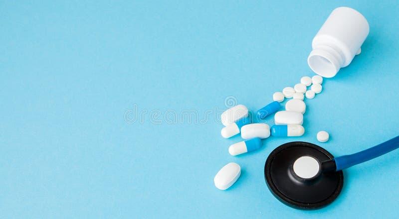 Abschluss herauf das Stethoskop und Pillen, die aus Tablettenfläschchen auf blauem Hintergrund heraus verschüttet werden Medizin, stockbilder