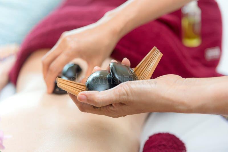 Abschluss herauf den heißen Stein, der sich zurück auf Frau der Haut hinlegt Asiatische Schönheitsfrau, die sich auf Massagebett  stockfoto