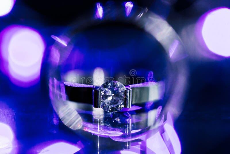 Abschluss herauf Diamantringehering innerhalb des Kreises Kreatives Heiratseinladungskartenkonzept Funkelnder purpurroter Hinterg stockbild