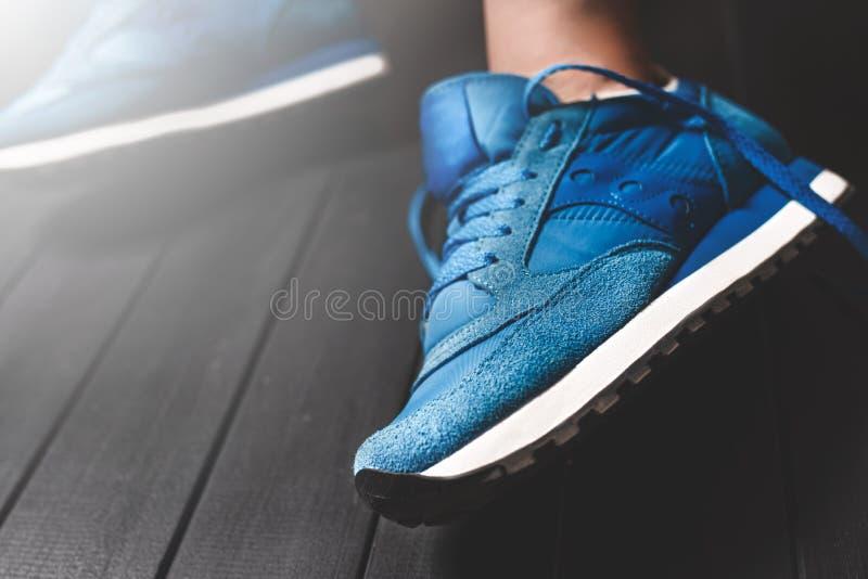 Abschluss herauf die Beine der Frauen auf hölzernem Hintergrund, blaue Turnschuhe, die Schuhe der Frauen, Stellenfokus Gelöste Sp lizenzfreies stockbild