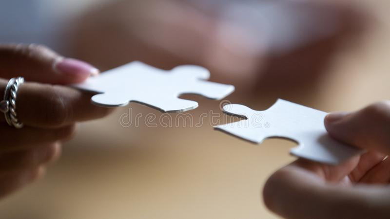 Abschluss herauf die gemischtrassigen Geschäftsteammitglieder, die Puzzlespielstücke anschließen lizenzfreies stockfoto