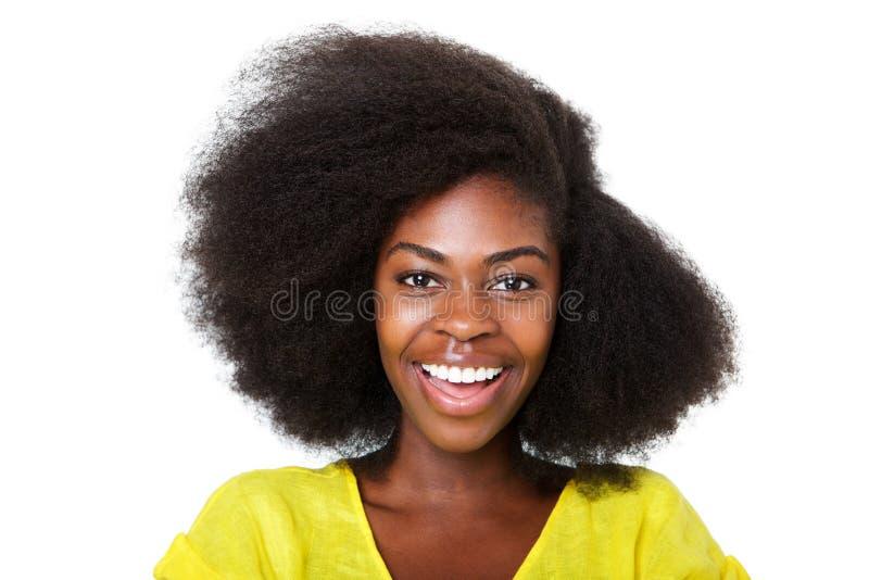 Abschluss herauf die glückliche junge Afroamerikanerfrau mit dem Afrohaar lachend gegen lokalisierten weißen Hintergrund lizenzfreie stockfotografie