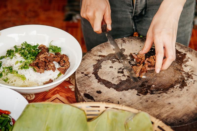 Abschluss herauf die Hände, die asiatischen Grill hacken, dämpfte Schweinefleisch auf altem hölzernem Schneidebrett für ReisNudel stockfoto
